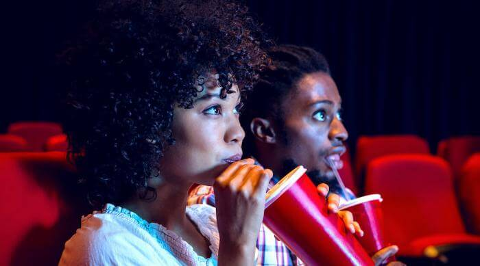 Shutterstock: Couple enjoying drinks at a movie theater together