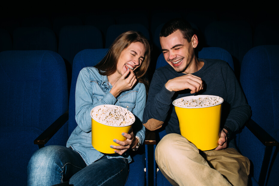 Shutterstock: Couple watching a movie and eating popcorn at theater