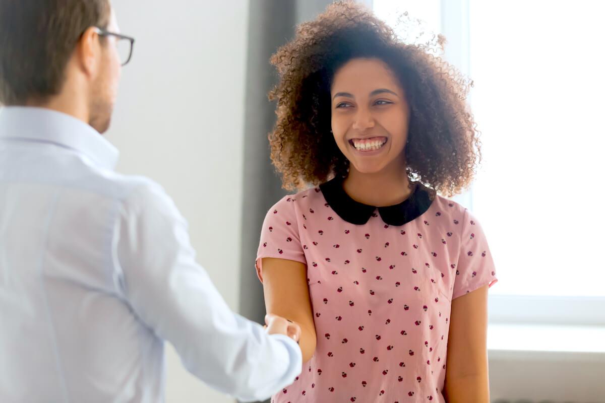shutterstock-woman-smiling-handshaking-man-meeting