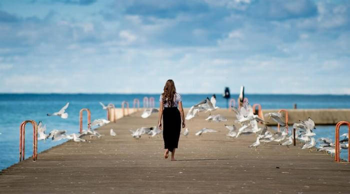 Unsplash: woman standing on dock with seagulls against blue cloudy sky