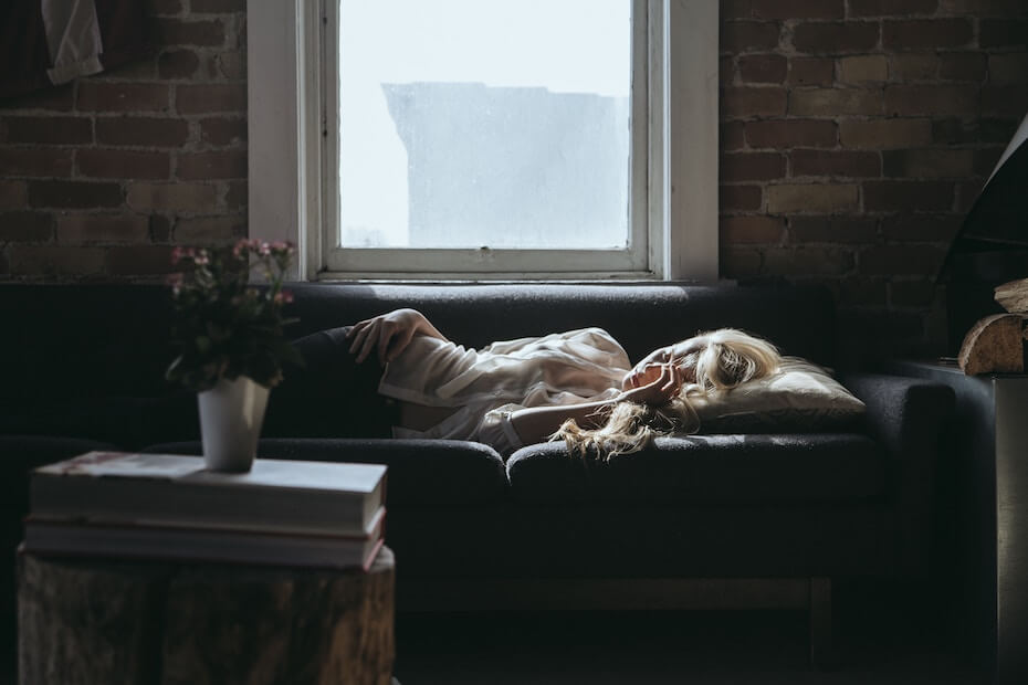 Unsplash: Woman sleeping on couch during day with hand on face