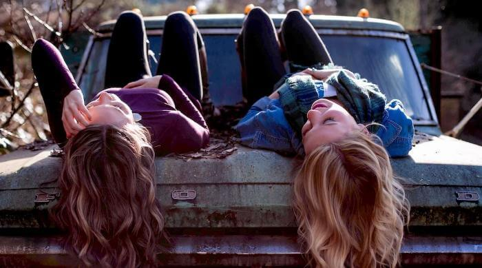 Unsplash: Friends talking and laying down on hood of truck