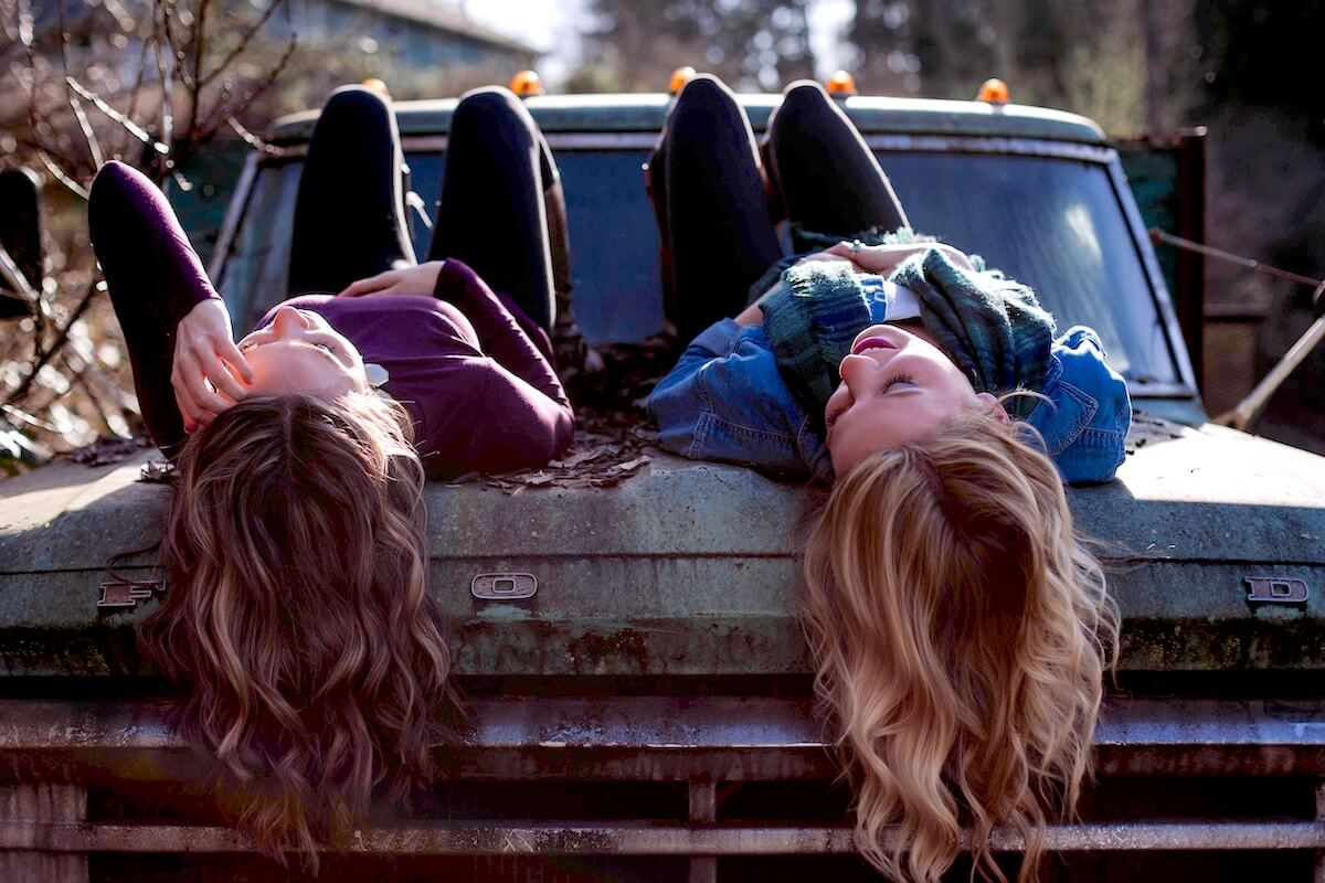 unsplash-greg-raines-friends-talking-on-truck-front