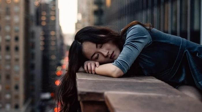 Unsplash: Woman leaning on balcony over city resting or sleeping