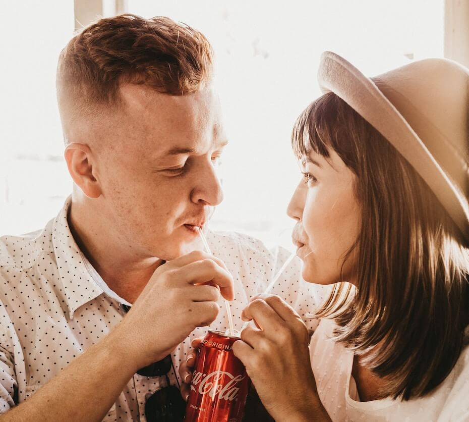 Unsplash: Man and woman sharing a can of soda on a date