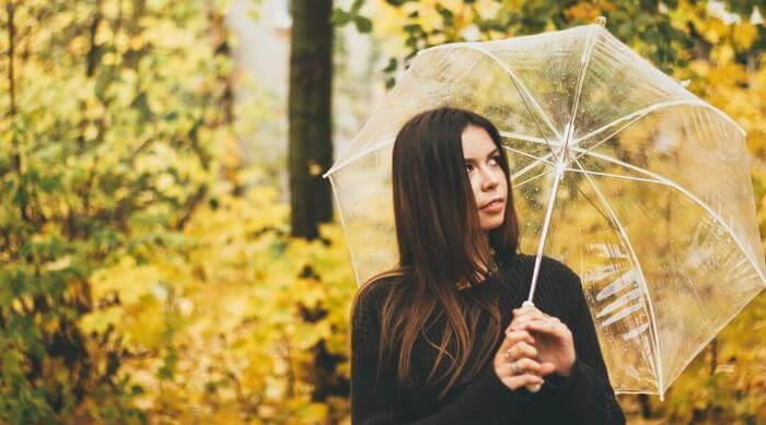 Unsplash: Woman with umbrella in the rain in a yellow forest