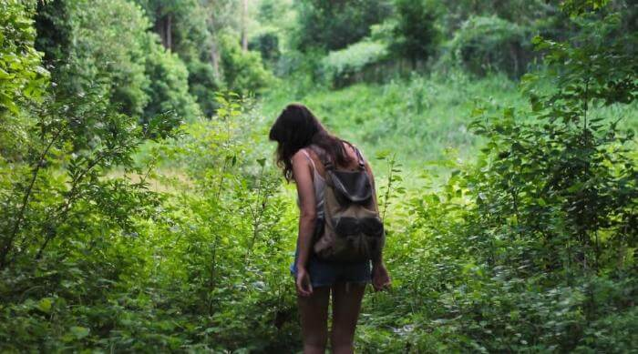 Unsplash: Woman adventuring backpacking through forest by herself alone