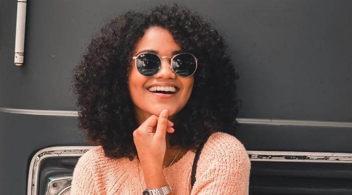 Unsplash: Woman smiling and posing wearing sunglasses in front of a Volkswagen bus