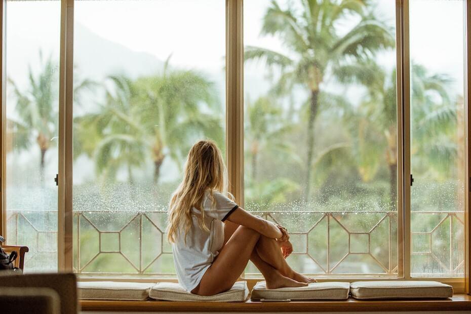 unsplash-roberto-nickson-woman-looking-out-rainy-window-stuck-bored-111119