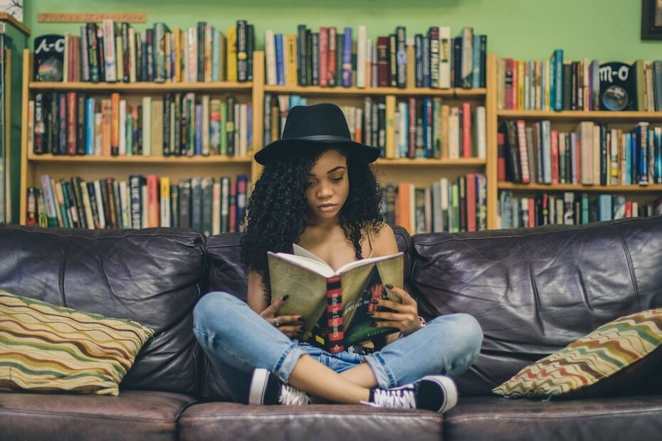 Unsplash: Woman sitting and reading a book in a library