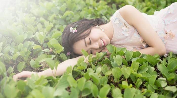 Unsplash: Woman in dress lying on clovers