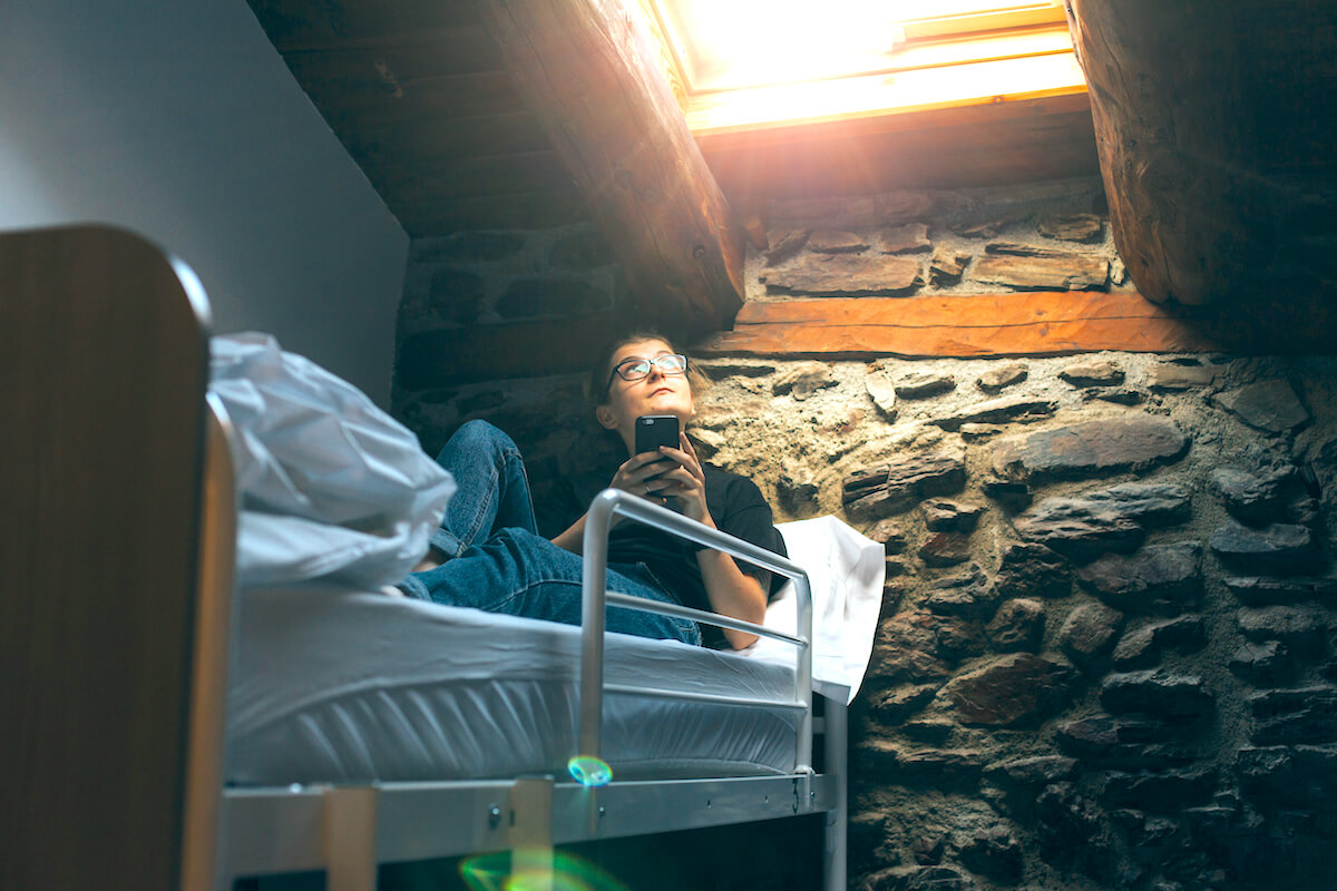 shutterstock-woman-on-phone-top-bunk-bed