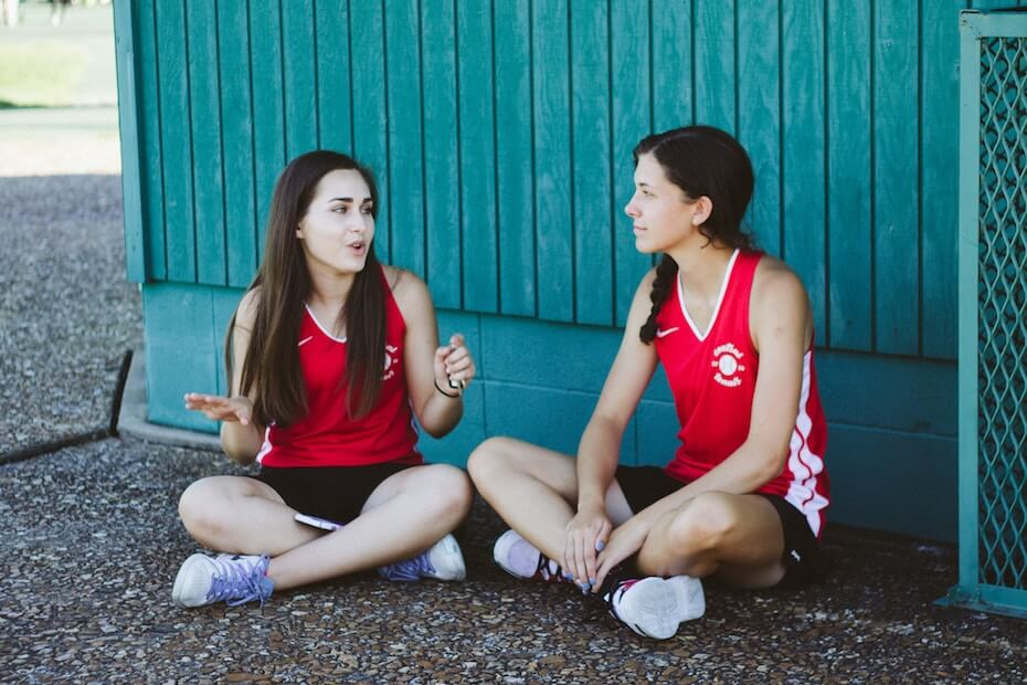 Unsplash: Two girls in basketball clothes PE sitting on ground talking
