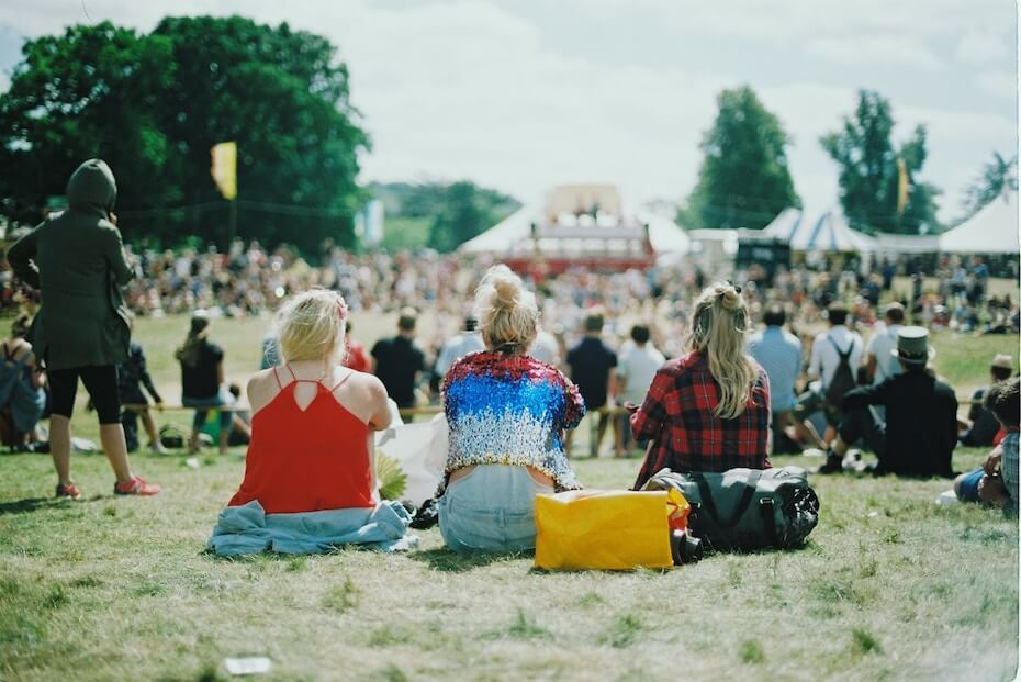 Unsplash: Woman with friends sitting on grass at music festival