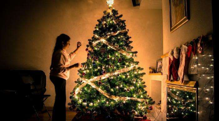 Unsplash: Christmas tree covered in lights with woman decorating