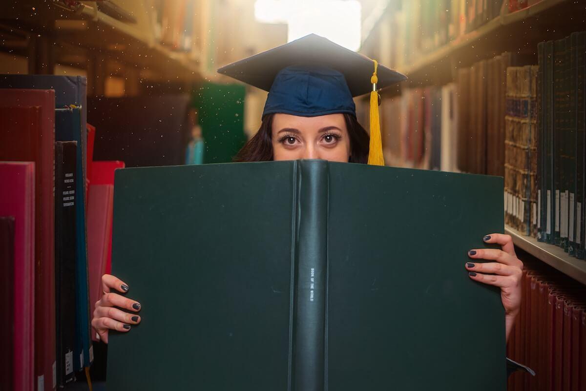 unsplash-jasmine-coro-woman-graduation-cap-library-with-book
