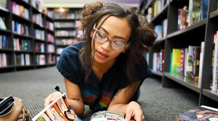 Unsplash: Woman with glasses reading comics on bookshop floor