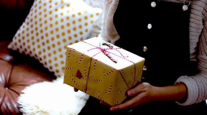 Unsplash: Woman holding up unwrapping a holiday gift box present