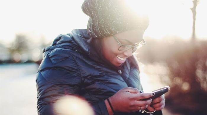 Unsplash: Woman smiling and texting looking at phone