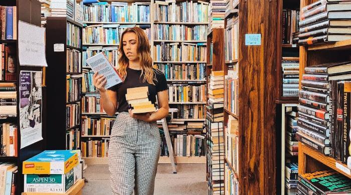 Unsplash: Woman in bookstore of library lots of books