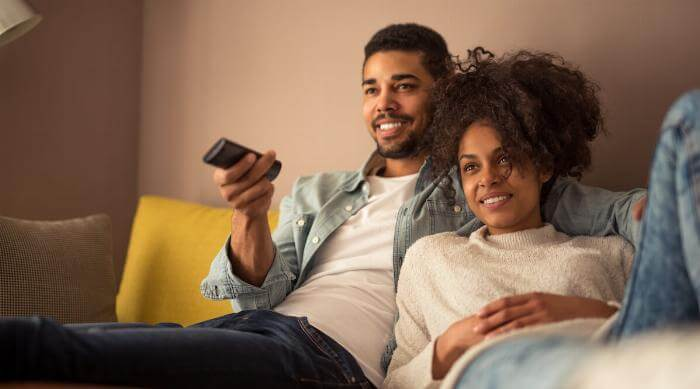 Shutterstock: Couple man and woman on couch watching TV