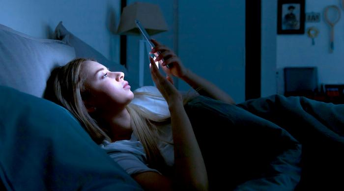 Shutterstock: Girl can't sleep looking at phone and texting in bed at night