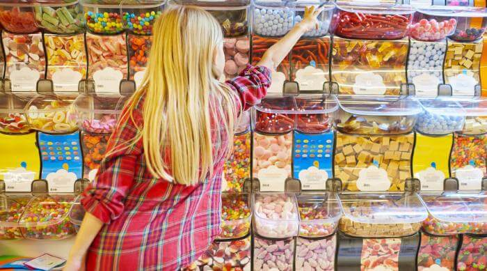 Shutterstock: Girl reading for treats at the candy store