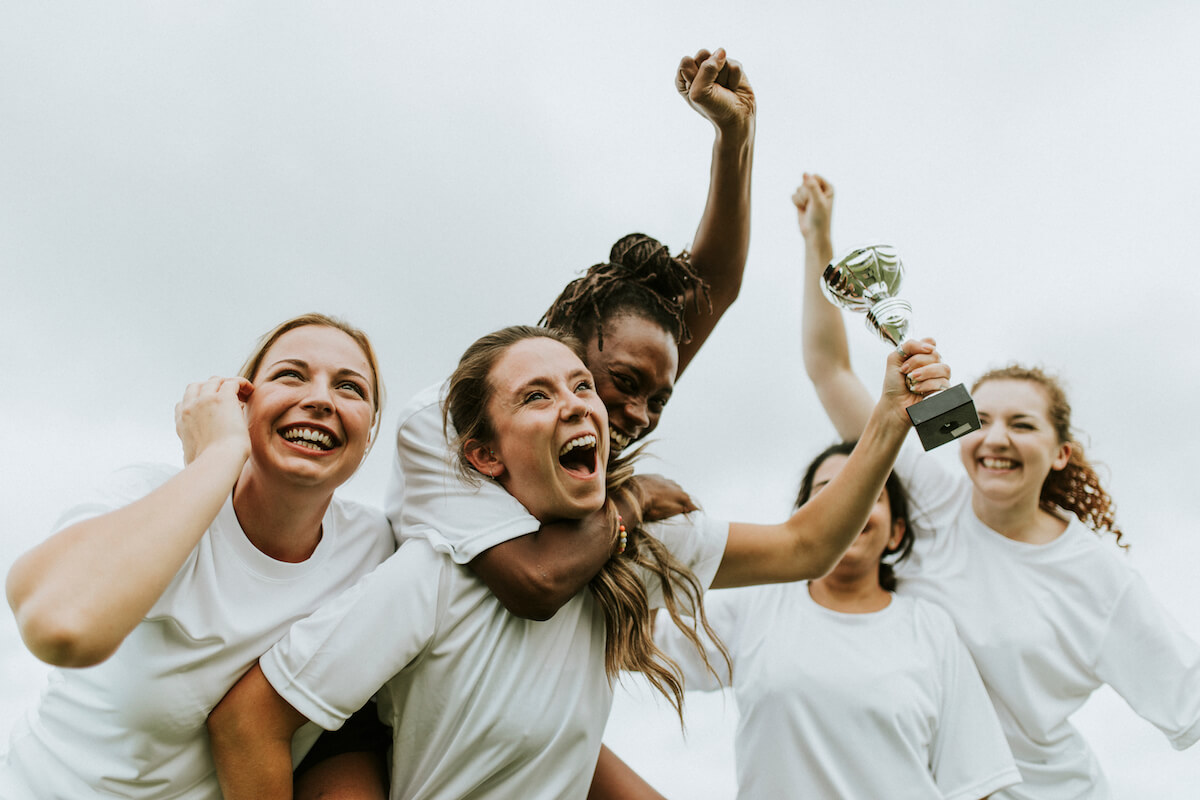 Shutterstock: Team of women winning soccer game holding up trophy