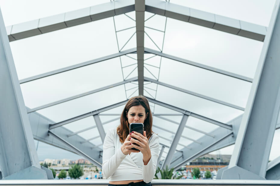 Shutterstock: Woman looking confused at her phone in a parking structure