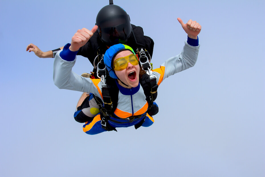 Shutterstock: Woman skydiving and giving thumbs up