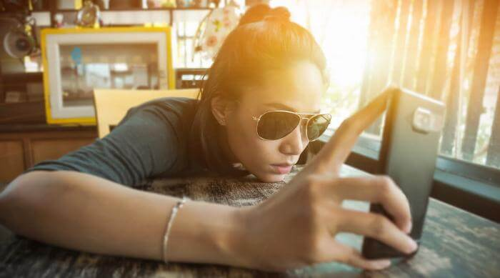 Shutterstock: Woman in sunglasses leaning over table looking at her phone bored