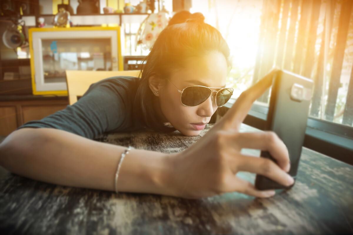 shutterstock-woman-sunglasses-looking-bored-at-phone