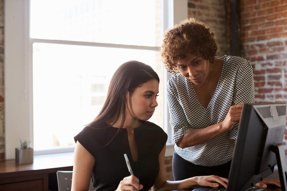 shutterstock-woman-working-on-computer-with-teacher-mentor-010220