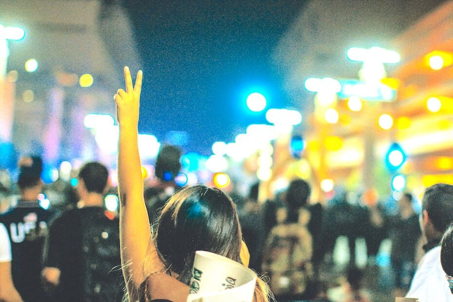 Unsplash: Woman marching in protest with peace sign