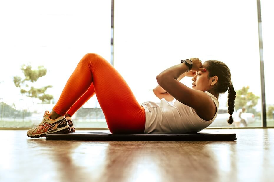 Unsplash: Woman working out doing situps indoors with athletic clothes