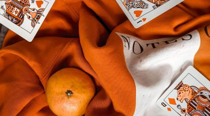Unsplash: Jack Queen and King of hearts on cloth with orange
