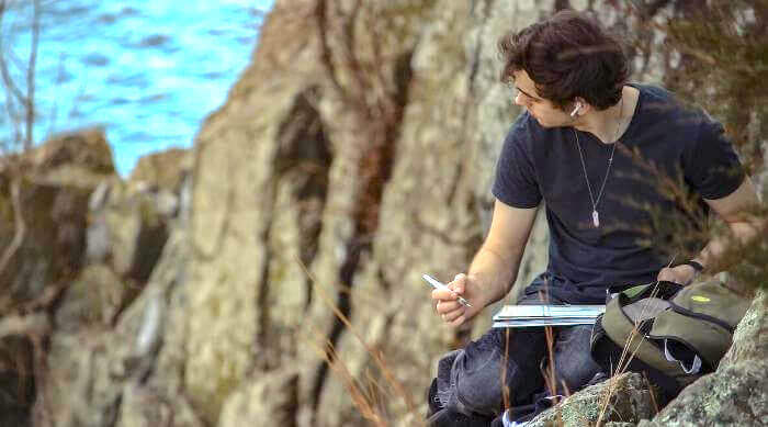 Unsplash: Man writing on paper in nature near mountains