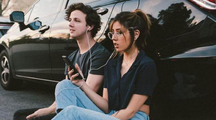 Unsplash: Couple man and woman listening with headphones to music from phone