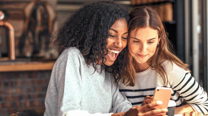Shutterstock: Friends laughing and sharing on a phone