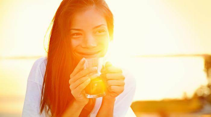 Shutterstock: Woman sipping a drink smiling at sunrise