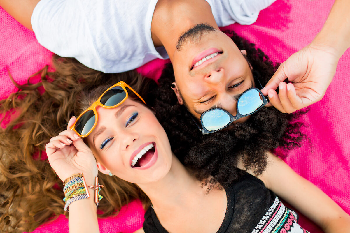 Shutterstock: Happy couple man and woman posing wearing sunglasses