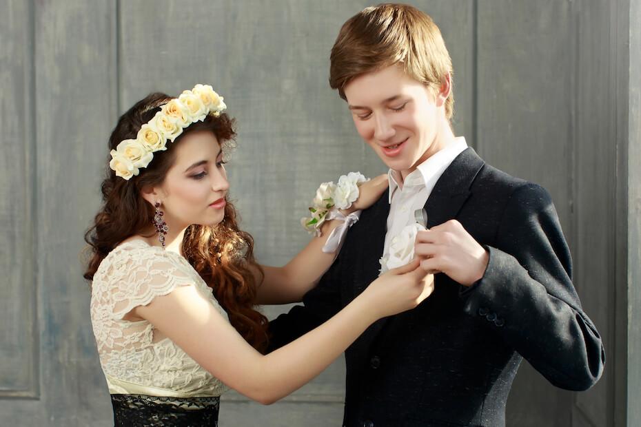 shutterstock-prom-couple-pinning-boutonniere-022820jpg