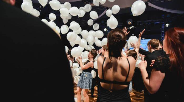 Shutterstock: Stepping onto dance floor at prom with falling balloons
