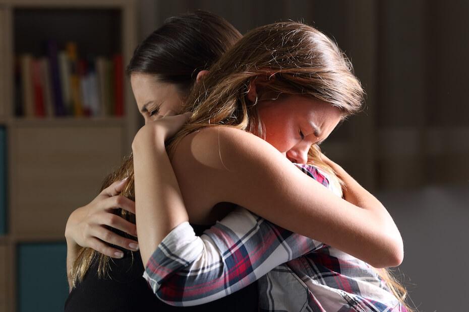 shutterstock-two-young-women-hugging-crying-sad-comforting-021020