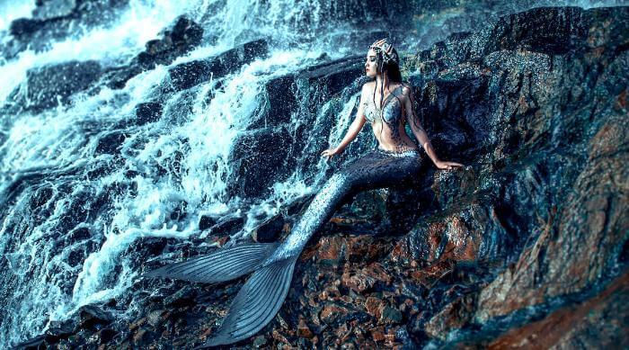 Shutterstock: Woman dressed as a mermaid bathing on rocks near waterfall