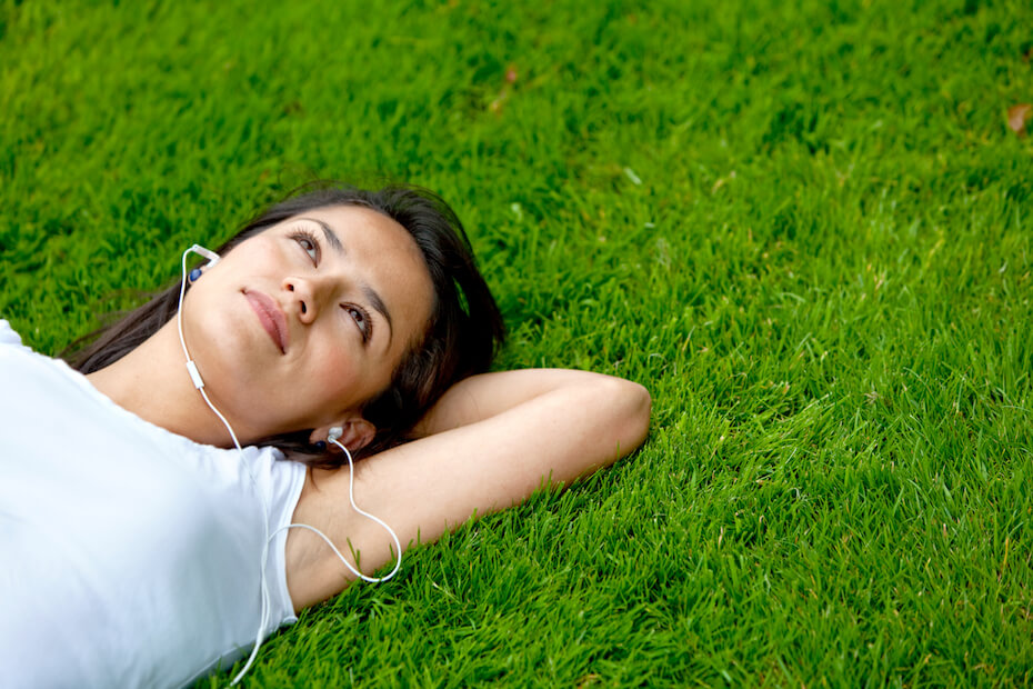 shutterstock-woman-listening-to-music-earbuds-in-grass-daydreaming-022420