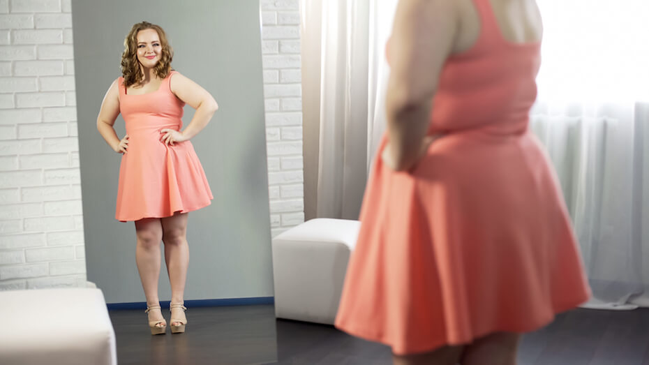 shutterstock-woman-looking-at-dress-in-mirror-body-positive-021320