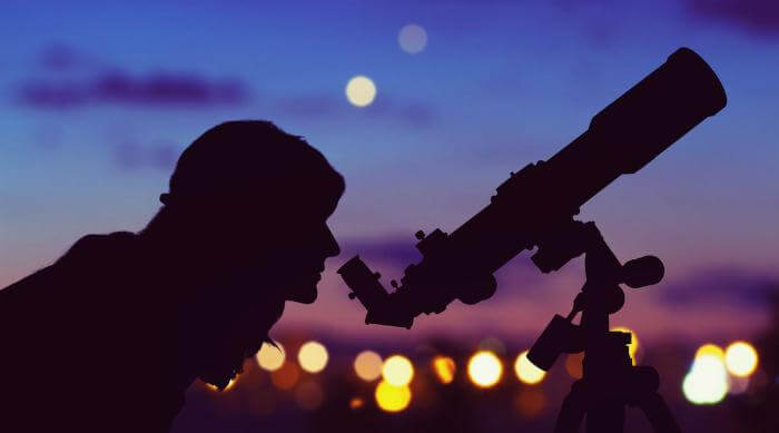 Shutterstock: Woman look up at stars through telescope