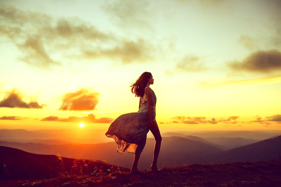 shutterstock-woman-standing-over-a-mountain-at-sunrise-021220
