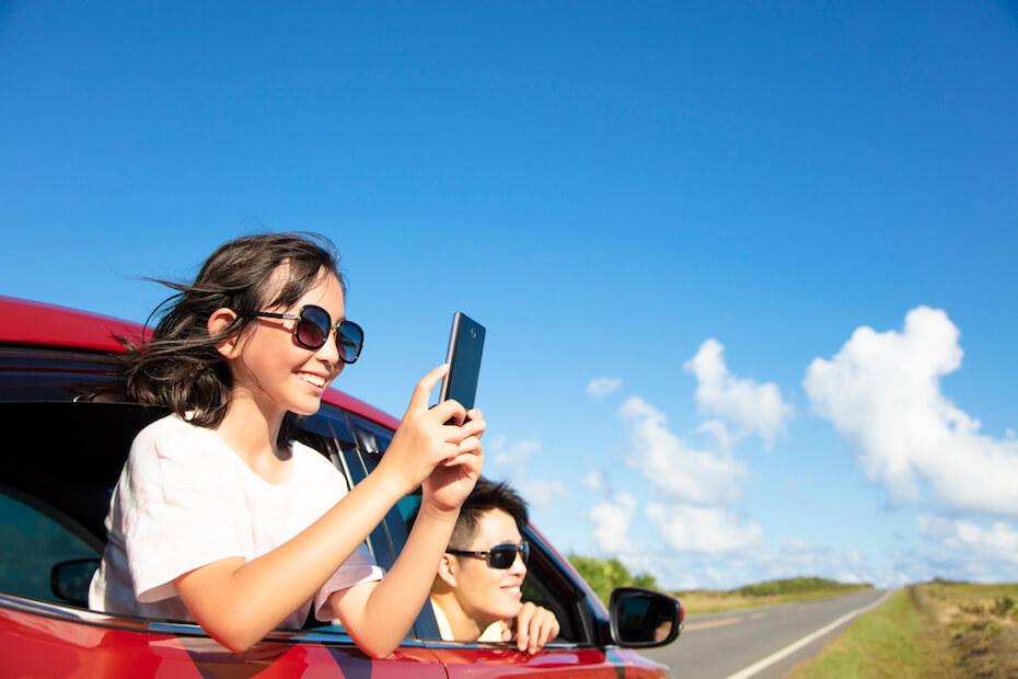 Shutterstock: Happy family enjoy road trip taking picture by smart phone